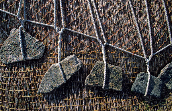 [BRITAIN.HEBRIDES 27693] 'Anker stones.'  	The thatched roof of the watermill of Great Bernera (an island off the north coast of Lewis) is held in place by elegantly knotted ropes and anker stones. Photo Mick Palarczyk.
