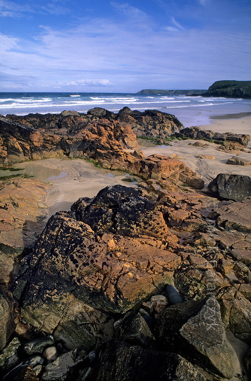 "[BRITAIN.HEBRIDES 27722] 'Orange and black rocks at Tolsta.'  	At Garry Beach near Tolsta, on the eastern shore of the Isle of Lewis, orange coloured rocks have received a striking ""painting"" by patches of black lichens. Photo Mick Palarczyk."