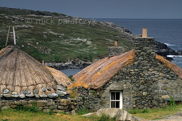 [BRITAIN.HEBRIDES 27708] 'Blackhouse in Gearrannan village.'  	The village of Gearrannan is located at a small bay on the northern coast of the Isle of Lewis. The last ageing residents left the 17th century village in the 1970s. It has now been lovingly restored and houses a youth hostel, self-catering accommodation and -seen here form the outside - a blackhouse which retains its original 1950s interior. Photo Mick Palarczyk.