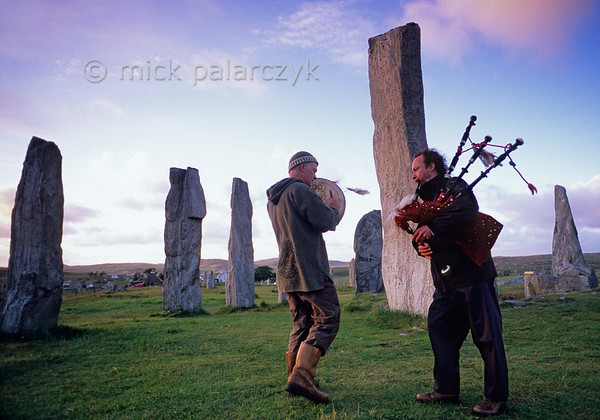 [BRITAIN.HEBRIDES 27671] 'Piping at Callanish stone circle .'  On a windy evening local musicians are enhancing the mystic atmosphere of the neolithic stone circle at Callanish on the Isle of Lewis. The tallest slab (just behind the piper) stands in the centre of the circle and marks the entrance to a burial chamber. Photo Mick Palarczyk.