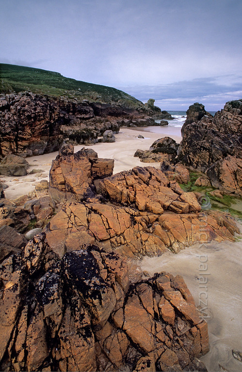 "[BRITAIN.HEBRIDES 27721] 'Orange and black rocks at Tolsta.'  	At Garry Beach near Tolsta, on the eastern shore of the Isle of Lewis, orange coloured rocks have received a striking ""painting"" by patches of black lichens. Photo Mick Palarczyk."