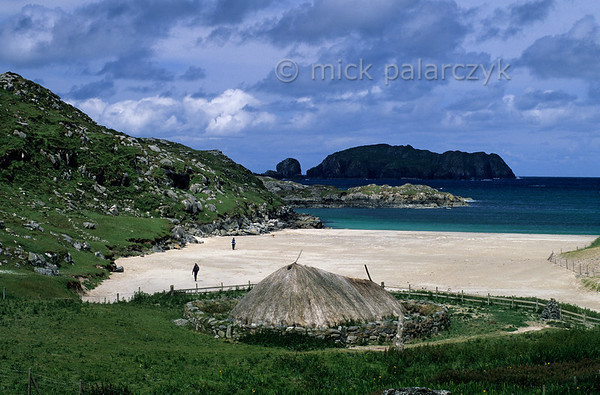 [BRITAIN.HEBRIDES 27698] 'Bosta Iron Age village.'  	At the beach of Bosta on Great Bernera (an island off the north coast of Lewis) a period of heavy storms in 1990s uncovered the stone remnants of Iron Age houses dating from 400 - 800 AD. The picture shows a 1999 re-construction of one of these houses. Photo Mick Palarczyk.