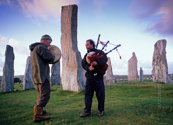 [BRITAIN.HEBRIDES 27672] 'Piping at Callanish stone circle.'  	On a windy evening local musicians are enhancing the mystic atmosphere of the neolithic stone circle at Callanish on the Isle of Lewis. The tallest slab stands in the centre of the circle and marks the entrance to a burial chamber. Photo Mick Palarczyk.