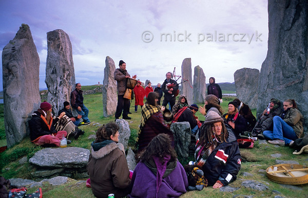 """[BRITAIN.HEBRIDES 27676] 'The Stonehenge of Scotland.'  On the Isle of Lewis the neolithic stone circle at Callanish has been called """"Scotland's Stonehenge"""". Just as its English counterpart, on the evening of june 21th it receives a variety people who want to celebrate the summer solstice. On the foreground people are sitting and dancing in the burial chamber that occupies the center of the stone circle. The girl with the hat is checking if the sun has already disappeared below the horizon. Photo Mick Palarczyk."""