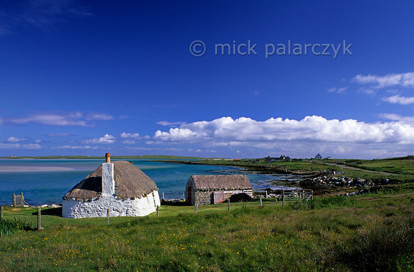 [BRITAIN.HEBRIDES 27736] 'Cottage on North Uist.'  Near Malacleit a thatched cottage overlooks a bay on the northern coast of the Isle of North Uist. Photo Mick Palarczyk.
