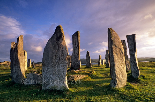 [BRITAIN.HEBRIDES 27670] 'Callanish stone circle.'  On the Isle of Lewis the standing stones of the neolithic stone circle at Callanish bask in the evening sun. The circle has a diameter of 13 meter and was constructed around 2700 BC from slabs of Lewisian gneiss. In the centre of the circle the tallest of the stones marks the entrance to a burial chamber. Photo Mick Palarczyk.