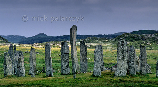 [BRITAIN.HEBRIDES 27675] 'Callanish seen from the east.'  The neolithic stone circle at Callanish was constructed around 2700 BC on the shore of East Loch Roag, an estuary along the north coast of Lewis. The tallest slab stands in the centre of the circle and marks the entrance to a burial chamber. Photo Mick Palarczyk.