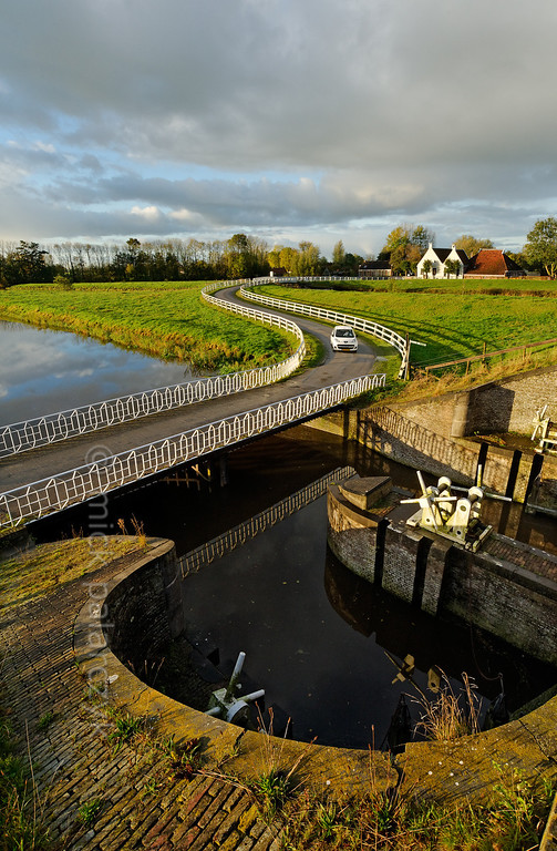 [HOLLAND.GRONINGEN 29429] 'Sluice at Aduarderzijl.'  A small country road crosses the Aduarderdiep at Aduarderzijl. The canal was dug in the 14th century under the direction of the monastery at Aduard to drain the lands near the town of Groningen. The excess water empties into the Reitdiep river by way of the sluice which can be seen in the foreground. Photo Mick Palarczyk.