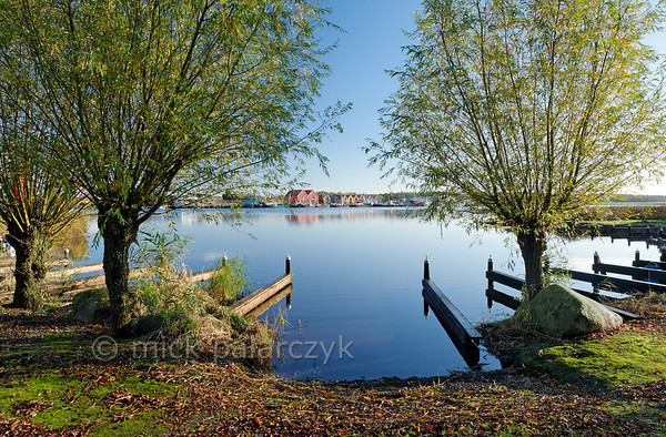 [HOLLAND.GRONINGEN 29444] 'Reitdiep at Zoutkamp.'  	Willows line the southern bank of the Reitdiep river at Zoutkamp. On the opposite bank the brightly coloured wooden houses of Zoutkamp can be seen. The Reitdiep formed the only navigable waterway between the sea and the town of Groningen till well into 19th century. Photo Mick Palarczyk.