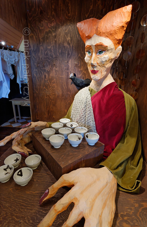 "[HOLLAND.GRONINGEN 29456] 'Tea museum in Houwerzijl.'  	A former church building in the village of Houwerzijl houses the ""Theefabriek"", a combination of teahouse and tea museum. Here we see a somewhat grotesque portrayal of a fortuneteller who is into reading tea leaves. The cups hold different patterns of tea leaves, such as cross, key, anchor and mill shapes, each having its proper significance for the future. Photo Mick Palarczyk."