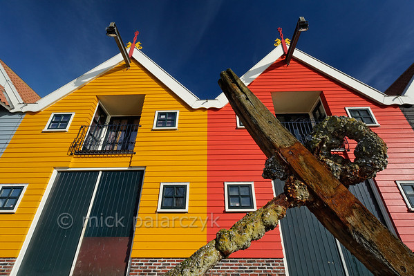 [HOLLAND.GRONINGEN 29443] 'Wooden houses in Zoutkamp.'  	Brightly coloured wooden houses in the harbour of Zoutkamp line the quay of the Reitdiep river. Photo Mick Palarczyk.