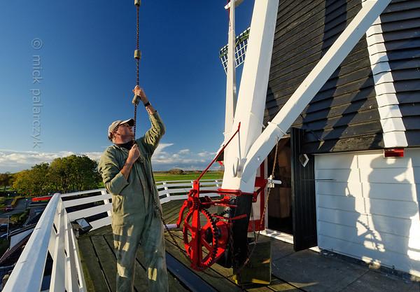 [HOLLAND.GRONINGEN 29500] 'Windmill De Kievit in Grijpskerk'  The miller of windmill De Kievit (The Lapwing) in Grijpskerk is operating the braking mechanism (Dutch: vang) of the mill. The wooden tower mill (Dutch: stellingmolen) was built in 1899 and has working corn grinding machinery. Photo Mick Palarczyk.