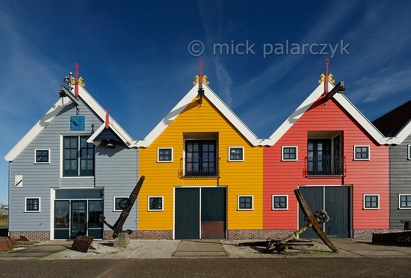 [HOLLAND.GRONINGEN 29442] 'Wooden houses in Zoutkamp.'  	Brightly coloured wooden houses in the harbour of Zoutkamp line the quay of the Reitdiep river. Photo Mick Palarczyk.