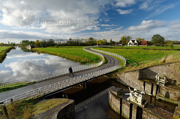 [HOLLAND.GRONINGEN 29432] 'Sluice at Aduarderzijl.'  	A small country road crosses the Aduarderdiep at Aduarderzijl. The canal was dug in the 14th century under the direction of the monastery at Aduard to drain the lands near the town of Groningen. The excess water empties into the Reitdiep river by way of the sluice which can be seen in the foreground. Photo Mick Palarczyk.