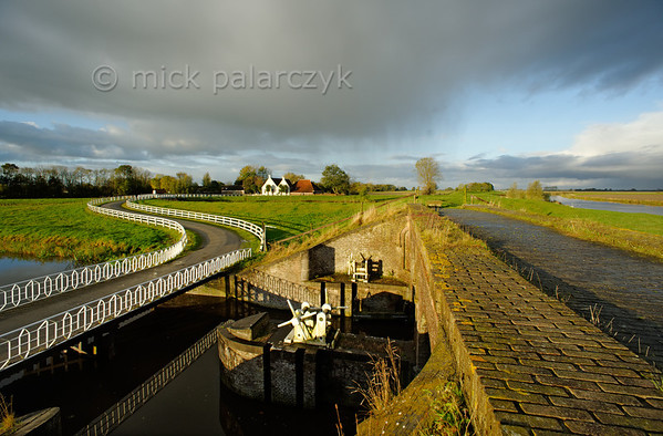 [HOLLAND.GRONINGEN 29431] 'Sluice at Aduarderzijl.'  	At Aduarderzijl a sluice connects the Aduarderdiep canal (left, in the foreground) to the Reitdiep river (on the right). The canal was dug in the 14th century under the direction of the monastery at Aduard to drain the lands near the town of Groningen. Photo Mick Palarczyk.