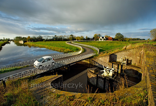 [HOLLAND.GRONINGEN 29427] 'Sluice at Aduarderzijl.'  	A small country road crosses the Aduarderdiep at Aduarderzijl. The canal was dug in the 14th century under the direction of the monastery at Aduard to drain the lands near the town of Groningen. The excess water empties into the Reitdiep river by way of the sluice which can be seen on the right-hand side of the picture. Photo Mick Palarczyk.