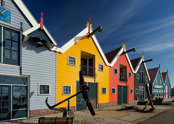 [HOLLAND.GRONINGEN 29441] 'Wooden houses in Zoutkamp.'  	Brightly coloured wooden houses in the harbour of Zoutkamp line the quay of the Reitdiep river. Photo Mick Palarczyk.
