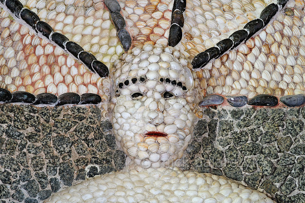 [HOLLAND.GRONINGEN 29488] 'Mermaid's head in shell grotto at Leek.'  	The interior of a garden-house on the Nienoord Estate near the village of Leek has been decorated with mosaics of mollusks around 1700 AD by Italian craftsmen. Here we see the head of a mermaid which occupies an alcove in the western wall. It is largely filled out with local Dutch shells but elsewhere tropical specimens have been used. Photo Mick Palarczyk.