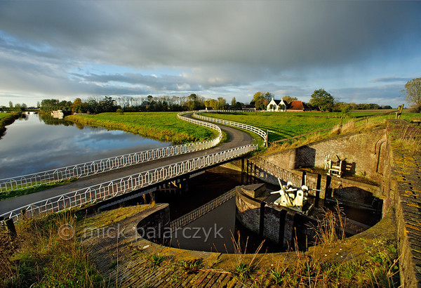 [HOLLAND.GRONINGEN 29428] 'Sluice at Aduarderzijl.'  	A small country road crosses the Aduarderdiep at Aduarderzijl. The canal was dug in the 14th century under the direction of the monastery at Aduard to drain the lands near the town of Groningen. The excess water empties into the Reitdiep river by way of the sluice which can be seen on the right-hand side of the picture. Photo Mick Palarczyk.