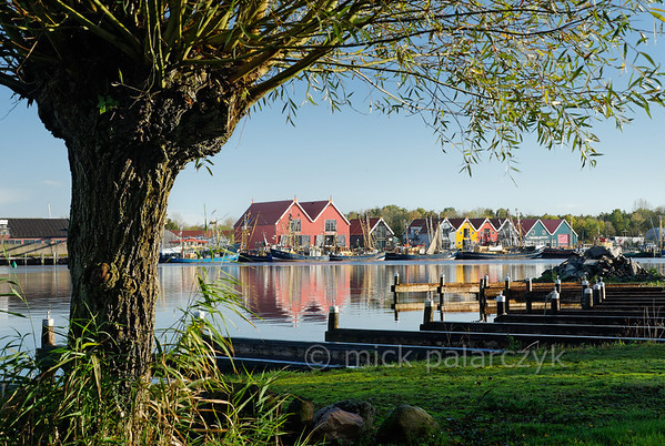 [HOLLAND.GRONINGEN 29446] 'Wooden houses in Zoutkamp.'  	Brightly coloured wooden houses in the harbour of Zoutkamp line the quay of the Reitdiep river. Photo Mick Palarczyk.