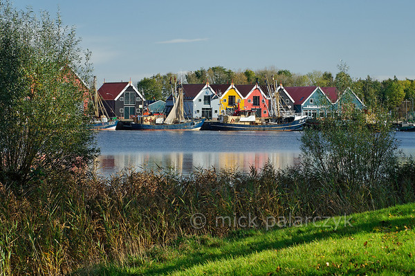[HOLLAND.GRONINGEN 29449] 'Wooden houses in Zoutkamp.'  	Wooden houses and fishing boats in the harbour of Zoutkamp line the quay of the Reitdiep river. Photo Mick Palarczyk.