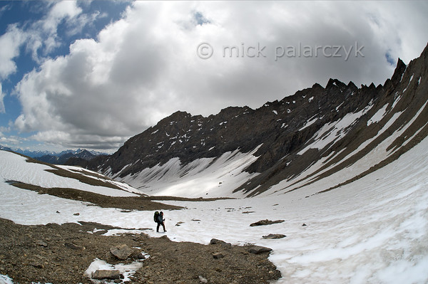Hiker in summer snow near Col Malatra.