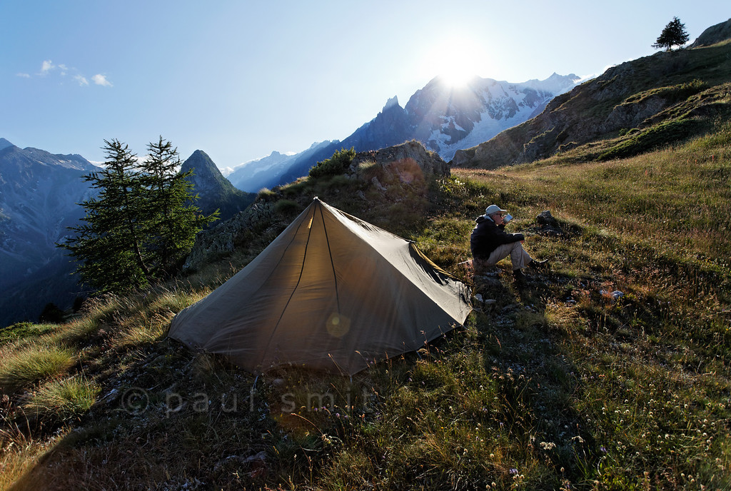 [ITALY.VALLEDAOSTA 28483 'Tent with a view of Mont Blanc.'  A hiker on the Tour du Mont Blanc trail has put up his tent just above the Rifugio Bertone mountain hut above Courmayeur, with the sun setting over the Mont Blanc. Photo Paul Smit.