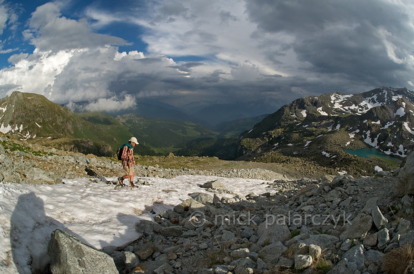 Hiker crossing snowfield above Lac de Tzan.