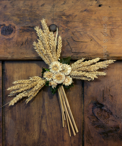 Cross made of wheat and dried flowers.