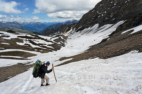 Hiker crossing summer snow near Col Malatra.
