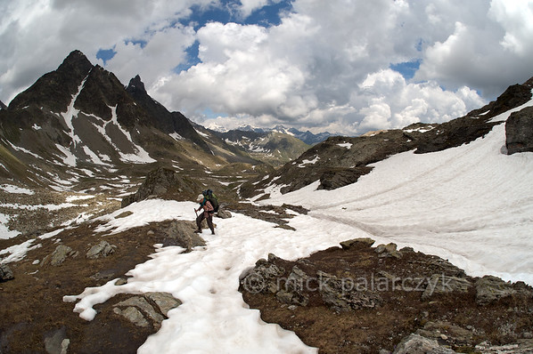 Hiker crossing snowfield at Fenêtre de Tzan.