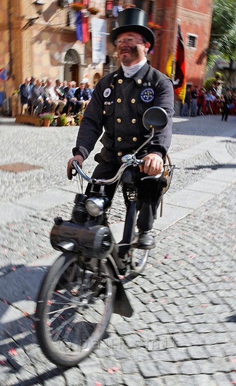 [ITALY.PIEMONTE 11077] 'Chimney sweeps parade in Santa Maria Maggiore.'  Chimney sweep Norbert Schwarzer from Göttingen in Germany on his Solex at the yearly parade of chimney sweeps in the streets of Santa Maria Maggiore. The parade is part of the International Chimney Sweeps Gathering (Raduno Internazionale dello Spazzacamino) in Valle Vigezzo. Photo Paul Smit.