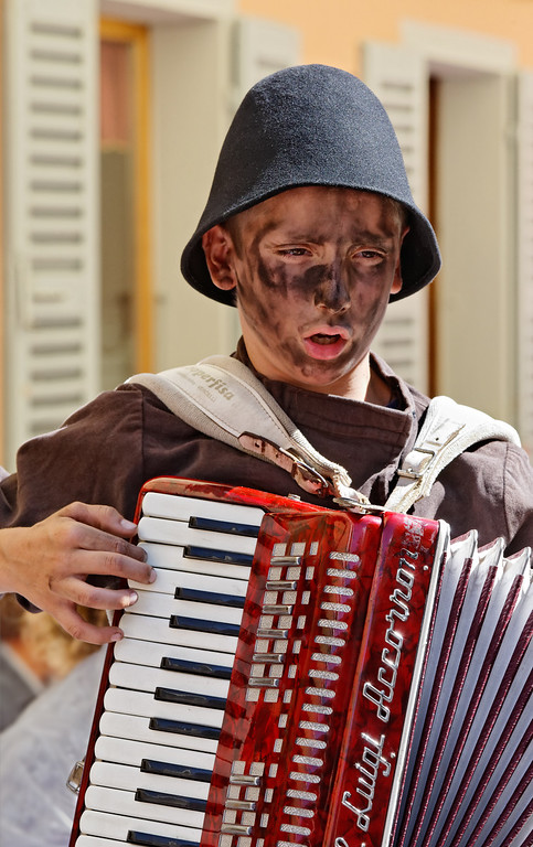 [ITALY.PIEMONTE 11082] 'Singing chimney sweep in Santa Maria Maggiore.'  During the International Chimney Sweeps Gathering (Raduno Internazionale dello Spazzacamino) in Valle Vigezzo a boy, dressed as chimney sweep, sings mostly sad songs of chimney sweep life. In the past Valle Vigezzo was extremely poor and many boys had to leave home in winter to live the hard and hungry life of chimney sweeps in the cities of the Po plain. Photo Paul Smit.