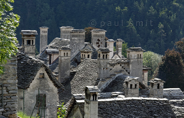 [ITALY.PIEMONTE 11092] 'Chimneys of Craveggia.'  Not only is Valle Vigezzo famous for its long history of chimney sweeps, its chimney sweep museum in Santa Maria Maggiore and its yearly International Chimney Sweep Gathering, its actual chimneys are worth a look as well. This sample is photographed in Craveggia. Photo Paul Smit.