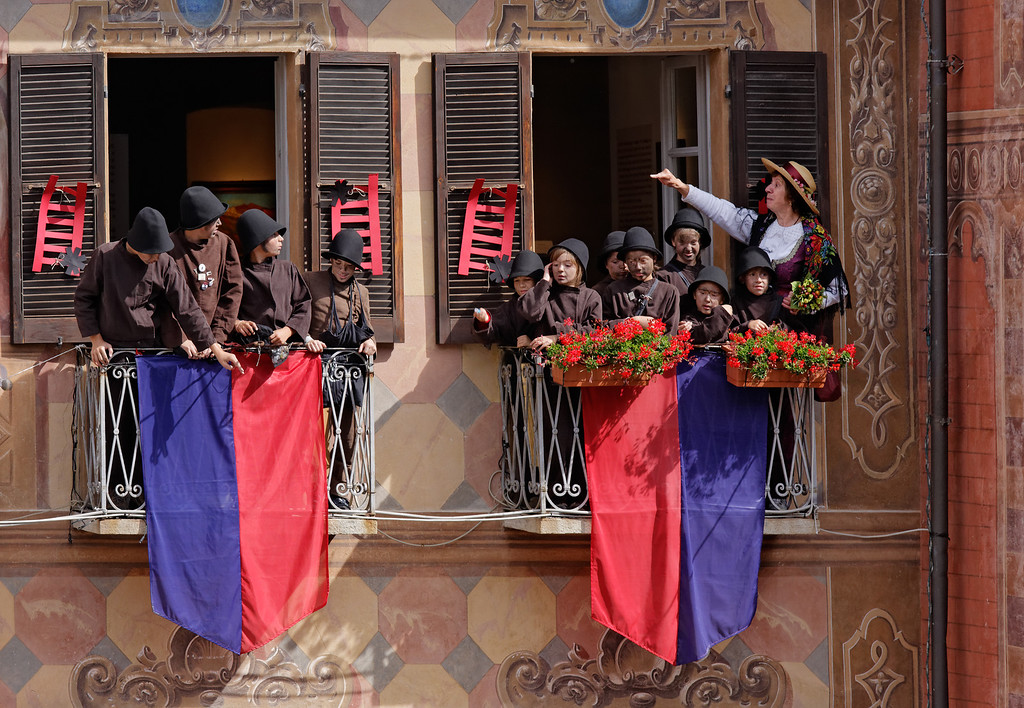 [ITALY.PIEMONTE 11084] 'Little chimney sweeps in Santa Maria Maggiore.'  Little chimney sweeps on the balconies of the town hall of Santa Maria Maggiore during the International Chimney Sweeps Gathering (Raduno Internazionale dello Spazzacamino) in Valle Vigezzo. Nowadays, as folklore, they look cute. But in the past Valle Vigezzo was extremely poor and many children (boys, not girls) had to leave home in winter to live the hard and hungry life of little chimney sweeps in the cities of the Po plain. Photo Paul Smit.