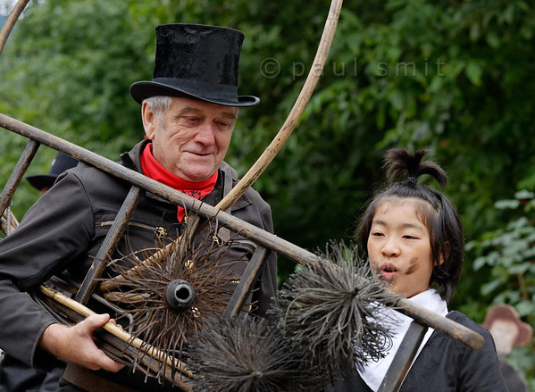 [ITALY.PIEMONTE 11050] 'Swiss chimney sweep with daughter of Japanese chimney sweep.'  The daughter of a Japanese chimney sweep is impressed by the old tools of a retired Swiss chimney sweep during the International Chimney Sweeps Gathering (Raduno Internazionale dello Spazzacamino) in Valle Vigezzo. Photo Paul Smit.