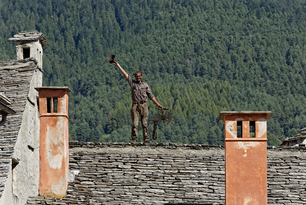 [ITALY.PIEMONTE 11085] 'Chimney sweep on the roofs of Santa Maria Maggiore.'  Livio Milani on a roof of Santa Maria Maggiore during the International Chimney Sweeps Gathering (Raduno Internazionale dello Spazzacamino) in Valle Vigezzo. As a child Livio has still climbed inside the chimneys to clean them, now he is  president of the National Association of Italian Chimney Sweeps. He lives and works in Valle Cannobina, a side valley of Valle Vigezzo. Photo Paul Smit.