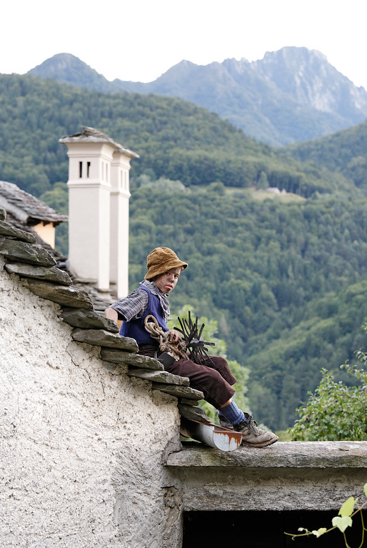 [ITALY.PIEMONTE 11059] 'Traditional little chimney sweep of Valle Vigezzo.'  Marco Pesenti from Malesco, photographed on the roofs of Villette, with the traditional clothes and tools of the little chimney sweeps of Valle Vigezzo from before 1940. In the old days it were mostly children who swept the chimneys by climbing up inside them and scraping them clean. Photo Paul Smit.