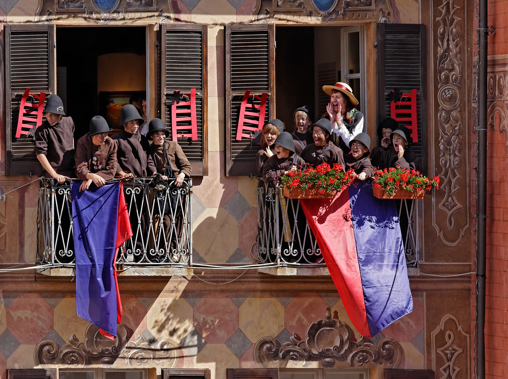 """[ITALY.PIEMONTE 11083] 'Little chimney sweeps in Santa Maria Maggiore.'  Little chimney sweeps on the balconies of the town hall of Santa Maria Maggiore during the International Chimney Sweeps Gathering (Raduno Internazionale dello Spazzacamino) in Valle Vigezzo. They are calling out loud """"spazzacaminooooo!"""", as they did in the old days, meaning so much as: """"Does anyone in this street needs his chimney sweeped?"""" Nowadays, as folklore, they look cute and happy. But in the past Valle Vigezzo was extremely poor and many children (boys, not girls) had to leave home in winter to live the hard and hungry life of little chimney sweeps in the cities of the Po plain. Photo Paul Smit."""