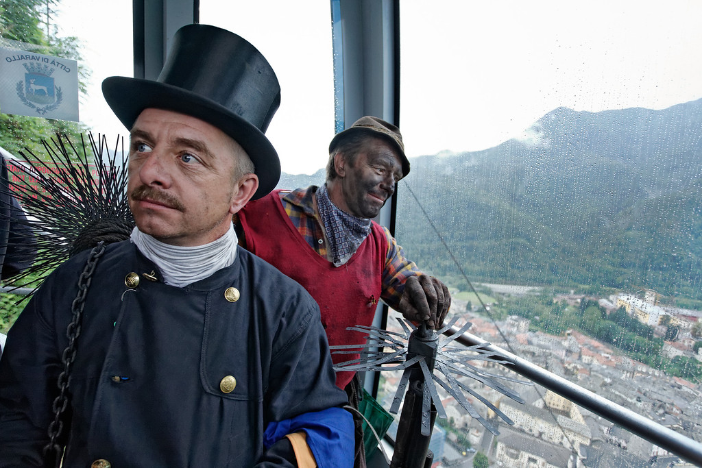 [ITALY.PIEMONTE 11091] 'Chimney sweeps in Varallo.'  Chimney sweeps in the cable-way to Sacro Monte, looking down at the rainy town of Varallo. They are having a day out from their International Chimney Sweeps Gathering (Raduno Internazionale dello Spazzacamino) in Valle Vigezzo, 80 km from Varallo. Photo Paul Smit.