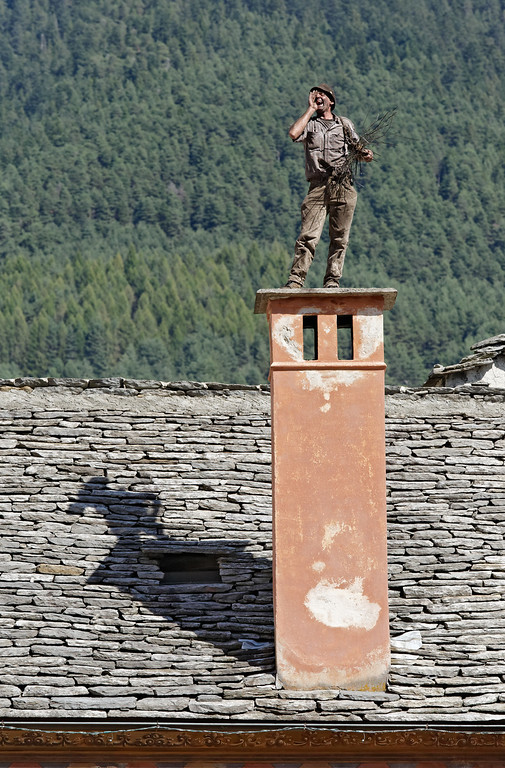 "[ITALY.PIEMONTE 11086] 'Chimney sweep on a chimney in Santa Maria Maggiore.'  Livio Milani on a chimney in Santa Maria Maggiore during the International Chimney Sweeps Gathering (Raduno Internazionale dello Spazzacamino) in Valle Vigezzo, calling out loud ""spazzacaminooooo!"", as did the Italian chimney sweeps in the old days. As a child Livio has still climbed inside the chimneys to clean them, now he is president of the National Association of Italian Chimney Sweeps. He lives and works in Valle Cannobina, a side valley of Valle Vigezzo. Photo Paul Smit."