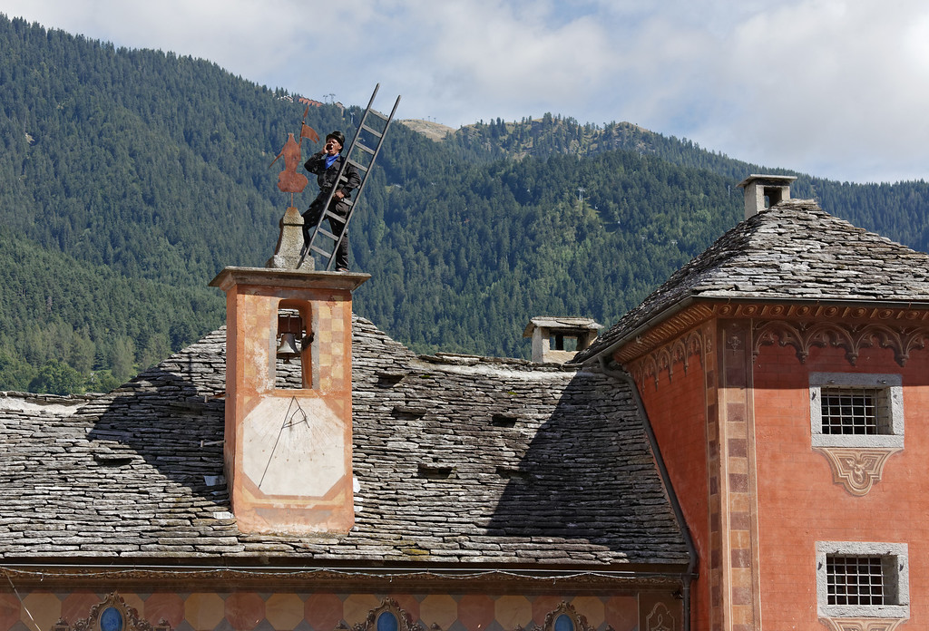 """[ITALY.PIEMONTE 11089] 'Chimney sweep on the roof of the town hall in Santa Maria Maggiore.'  Swedish chimney sweep on the roof of the town hall in Santa Maria Maggiore during the International Chimney Sweeps Gathering (Raduno Internazionale dello Spazzacamino) in Valle Vigezzo. In his best Italian he is calling out loud """"spazzacaminooooo!"""", as did the local chimney sweeps in the old days. Photo Paul Smit."""