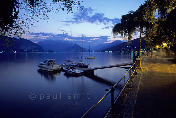 [ITALY.PIEMONTE 01623]  'Evening in Pallanza.'  After sunset sauntering is the thing to do along the boulevard of Pallanza, the prettiest town of the Verbania municipality. Although the saunterers have vanished in the long photo exposure, the film did register other typical mediterranean lakeshore ingredients. Photo Paul Smit.