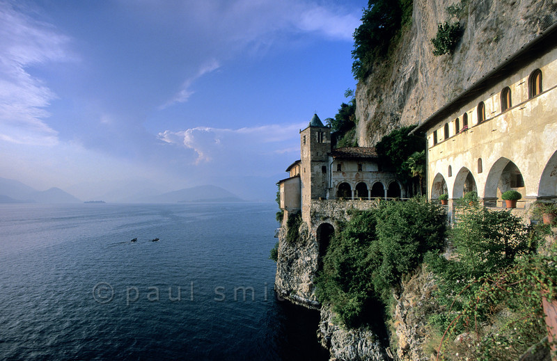 """[ITALY.LOMBARDIA 01808]  'Hermitage with a view.'  The Santa Caterina hermitage is built on a breathtaking spot halfway up a cliff over Lago Maggiore. Here a hermit once retreated in a cave. He helped people with spiritual advise and medical care. Asking what he wanted in return he said """"a chapel."""" Later a church and small monastery grew from it, still occupied by several lay brothers and sisters plus one friar and open to visitors. Photo Paul Smit."""