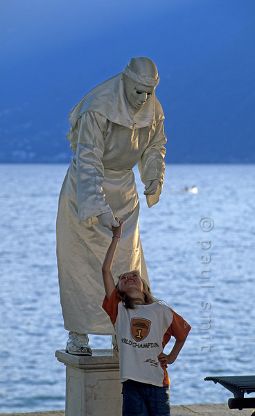[SWITZER.TICINO 01365]  'Living statue.'  Being timid at first, seeing the motionless statue at the boulevard of Ascona, the girl gained courage and asked for its hand. Although only coming into motion for money it couldn't resist her charm, bowed down and took her hand. Of sheer joy she then made a pirouette. Photo Paul Smit.