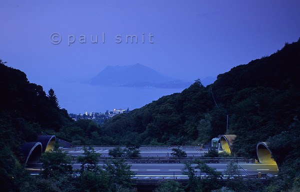 [ITALY.PIEMONTE 01731]  'Fast tunnels.'  Good motorway connections lead to the main tourist regions of Lago Maggiore around Locarno and Stresa (visible down below). Happily the 'autostrada' keeps ample distance to the beautiful shores and who chooses speed is more in then out of tunnels. Photo Paul Smit.