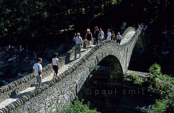 [SWITZER.TICINO 01322]  'Not a Roman bridge.'  The famous 'Roman Bridge' near Lavertezzo in Valle Verzasca actually dates from the Middle Ages. For its own good it attracts too manytourists and people who like to sunbath and swim in the Verzasca below it. Photo Paul Smit.