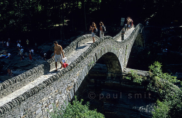[SWITZER.TICINO 01323]  'Not a Roman bridge.'  The famous 'Roman Bridge' near Lavertezzo in Valle Verzasca actually dates from the Middle Ages. For its own good it attracts too manytourists and people who like to sunbath and swim in the Verzasca below it. Photo Paul Smit.