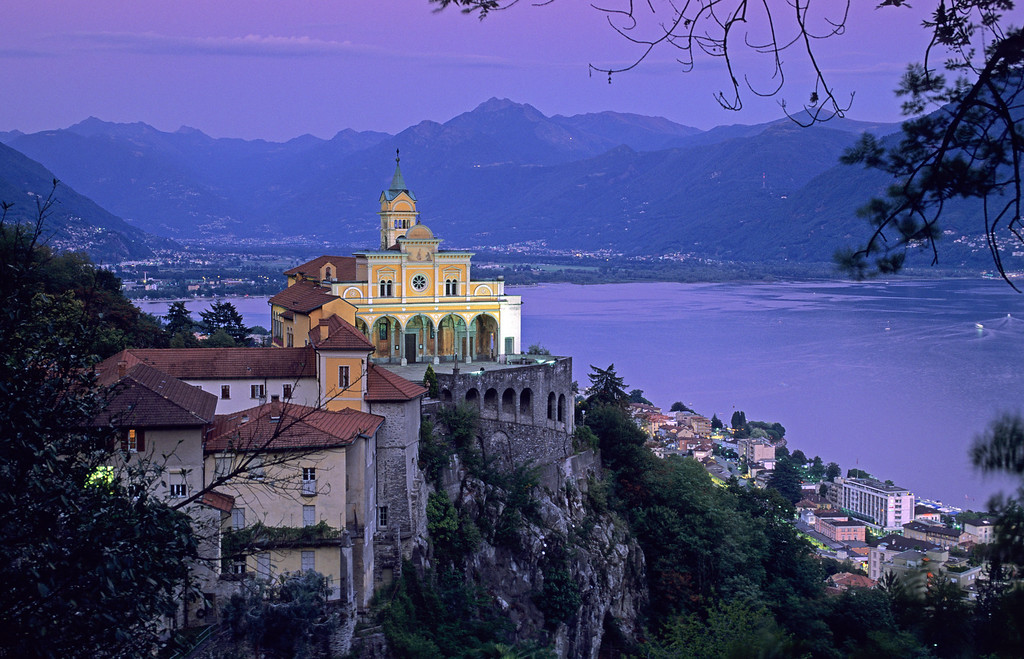 [SWITZER.TICINO 01350]  'Madonna del Sasso.'  Pilgrimage church Madonna del Sasso is the symbol of Locarno. In the evening, when the floodlights switch on and a string of lights embraces the Lago Maggiore, the spot has lost nothing of its original charm. A historical cable train brings you up. Photo Paul Smit.
