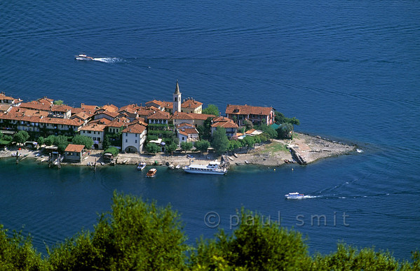 [ITALY.PIEMONTE 01628]  'Isola dei Pescatori.'  The only true village of the Borromeo Islands is situated on Isola dei Pescatori, the Fishermen's Island. Once only the fishermen from this island had the right to fish in the Lago Maggiore. Nowadays the inhabitants catch tourists in their fishrestaurants and souvenirshops. Between 11 am and 5 pm it's a kermis, but beyond and out of season it has lost little of its charm. Photo Paul Smit.